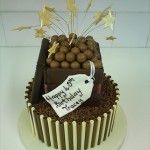 chocolate tube cake with top tier chocolate box, maltesers and stars on wires