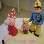 peppa pig, fireman sam and little girl on cake