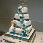 modern wedding cake with purple and turquoise flowers