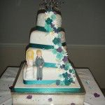 purple and turquoise wedding cake, with tumbling flowers