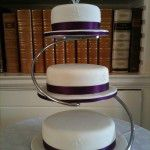 3 tier round cake on stand with burgundy ribbon and hearts on wires