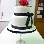 2 tier white cake, black polka dot ribbon and large red rose on top
