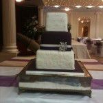 purple iced wedding cake with brooche