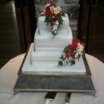 3 tier square cake with criss cross ribbons and red rose sprays