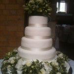 3 tier ivory cake with spots and fresh flowers