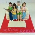 family sitting on a sofa cake