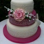 3 tier pink and ivory cake with vintage rose and bow with brooche