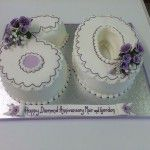 six and zero birthday cake with lilac edging and lilac flowers sprays