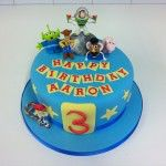 toy story cake with some handmade figures some plastic