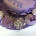 purple cake with butterflies, flowers and matching cupcakes