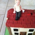 handmade model of builder on roof of house cake