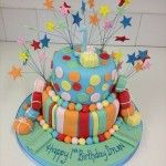 multicoloured first birthday cake with lots of stars on wires, stripes and spots