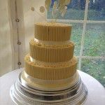 3 tier white chocolate cigarello tube cake with cirles on wires