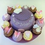 purple cake with cupcakes around the sides, butterflies, flowers and hearts
