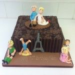 milk and dark tubes with handmade figures cake and eiffel tower