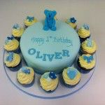 pale blue cake with handmade bear and matching cupcakes