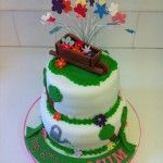 gardening cake 2 tier with wheel barrow on top and flowers on wires