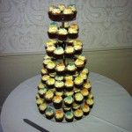 cupcake tower with yellow, orange and blue frangipani flowers