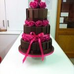 chocolate panel wedding cake with fresh flowers in between tiers