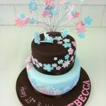 2 tier brown and pale blue cake with pink and blue flowers trailing down