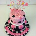 pink black and white two tier spots and stripes cake with sweets on wires